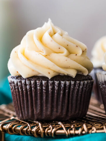 chocolate cupcake in a white liner topped with a pile of piped brown butter frosting