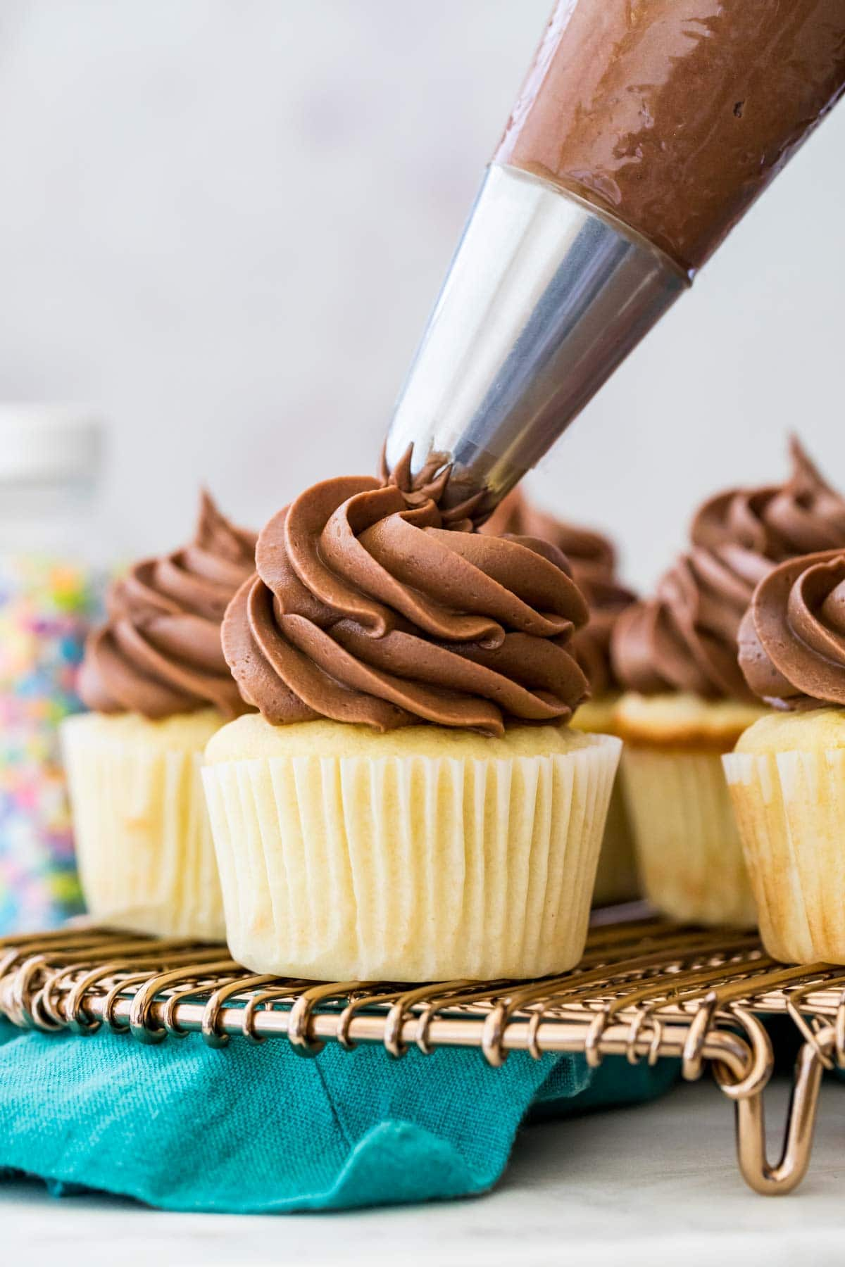 Piping chocolate frosting on a cupcake.