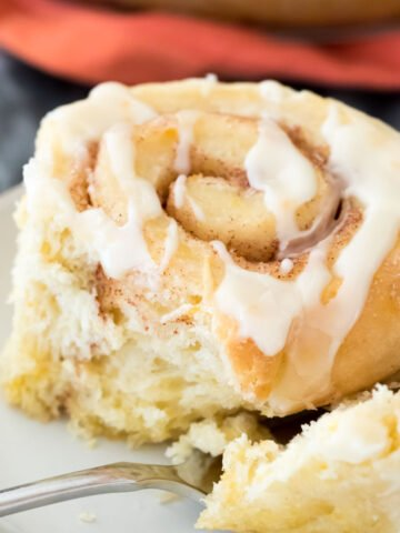 Closeup of orange sweet roll on white plate with a fork