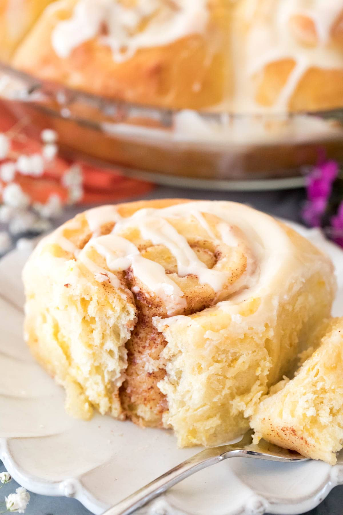 Closeup of iced orange sweet roll on a white plate