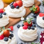 Mini pavlovas topped with whipped cream, strawberries, raspberries, and blueberries.