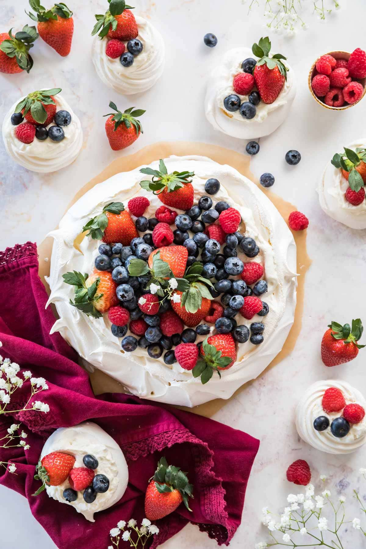 Large pavlova topped with fruit and whipped cream surrounded by mini pavlovas.
