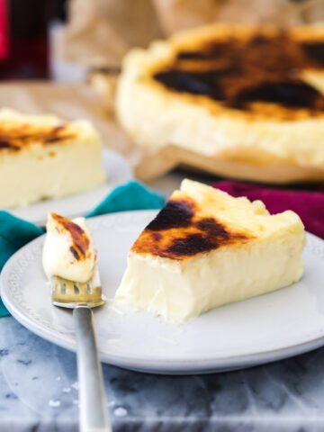 Basque cheesecake on white plate with a bite on a fork