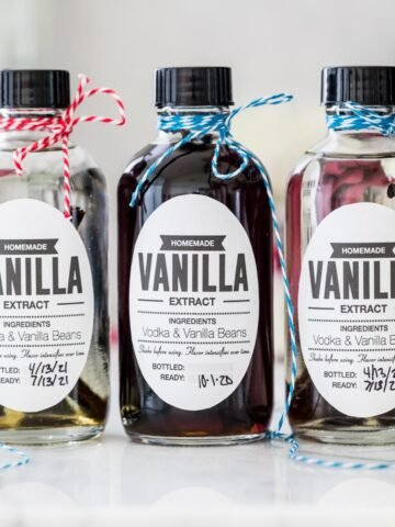 Three bottles of homemade vanilla extract with different color string on the tops
