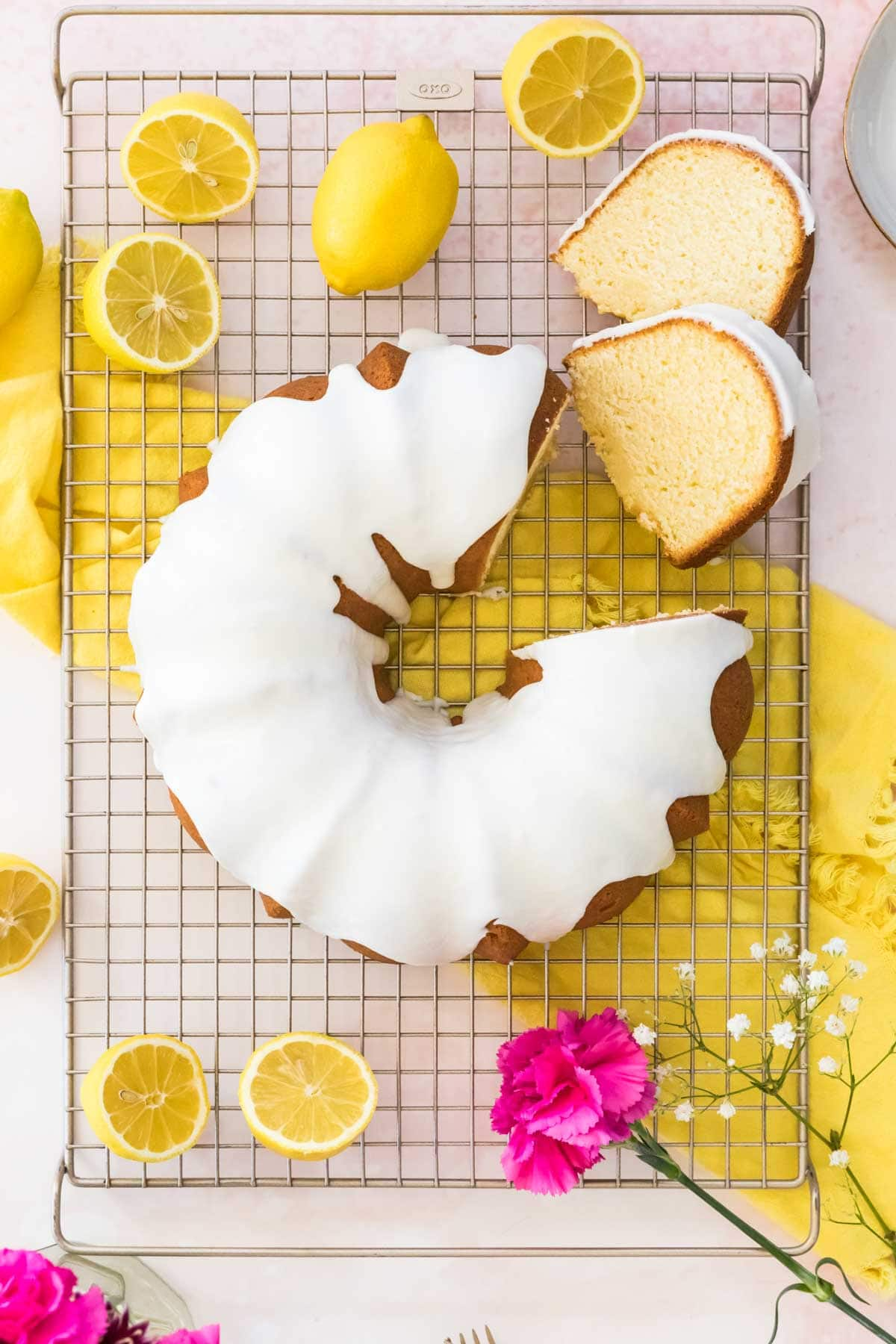 Overhead shot of lemon pound cake on a cooling rack with two pieces cut out and surrounded by cut lemons.