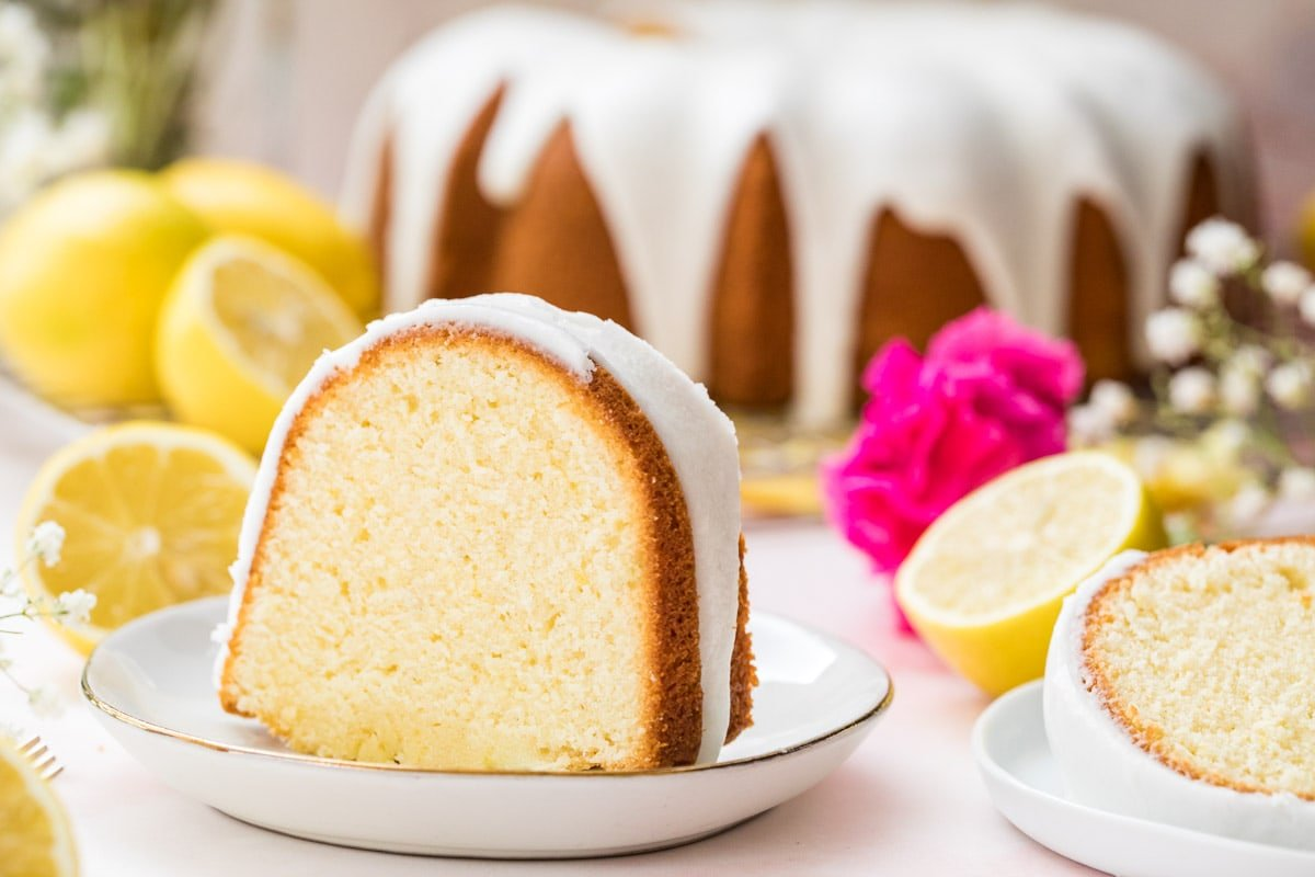 Lemon pound cake slice on a white plate with lemons and whole cake in the background.
