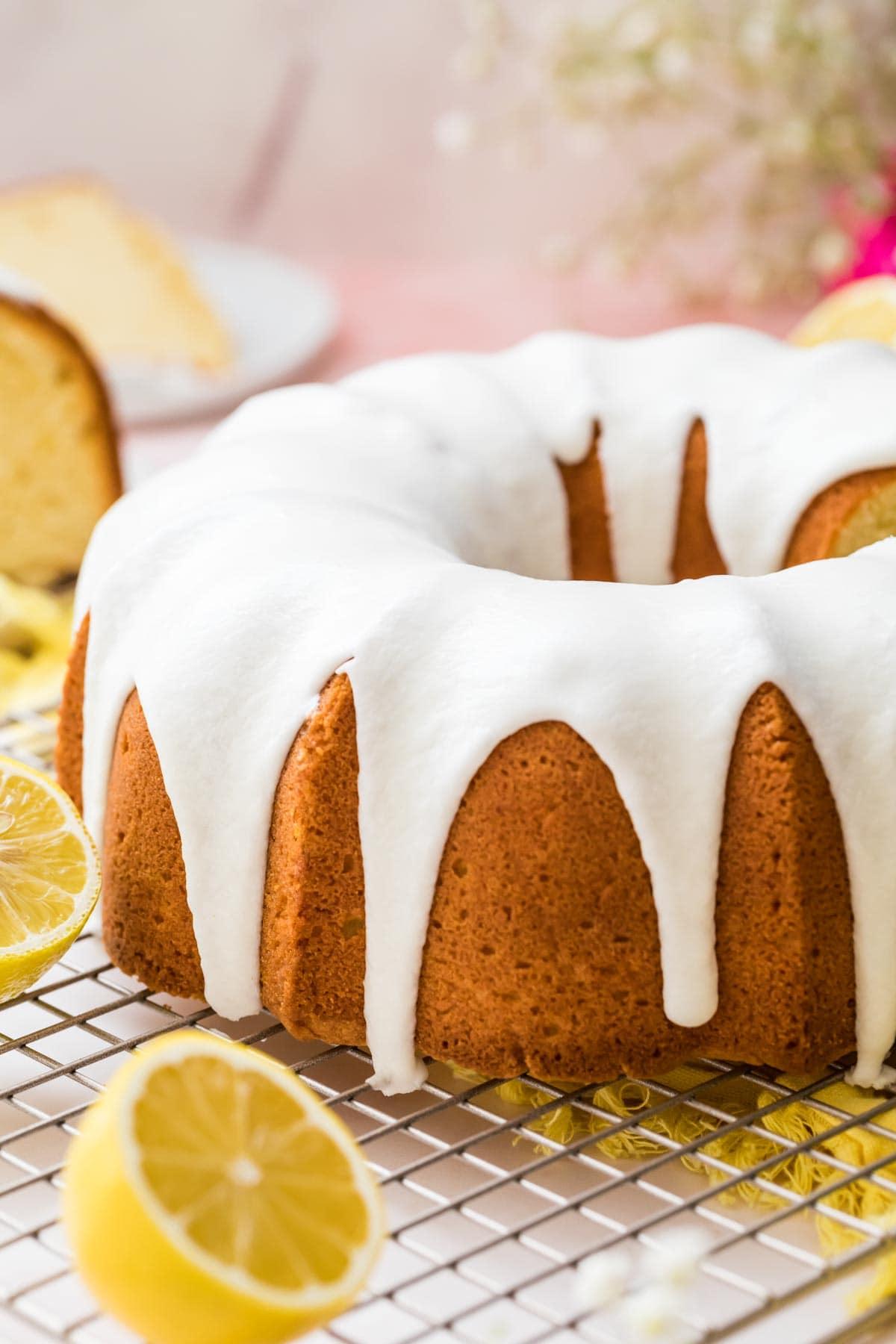 Lemon pound cake iced sitting on a cooling rack.