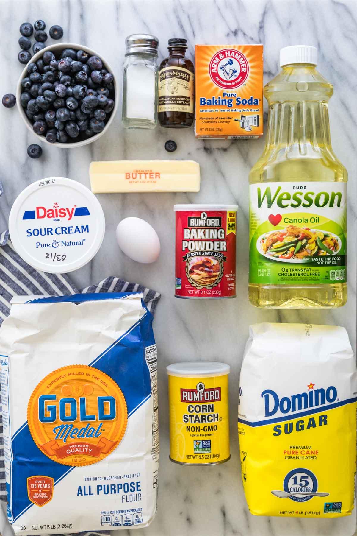 Ingredients for blueberry muffins: flour, cornstarch, sugar, canola oil, bakin gpowder, egg, sour cream, butter, baking soda, vanilla, salt, blueberries