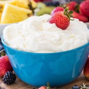 Fruit dip in a blue bowl with strawberries in it.