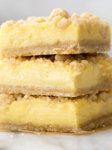 Three lemon crumb bars stacked on top of each other.