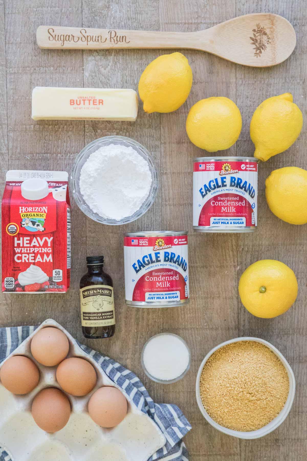 Wooden spoon, butter, lemons, powdered sugar, sweetened condensed milk, heavy cream, vanilla extract, eggs, granulated sugar, and graham cracker crumbs.