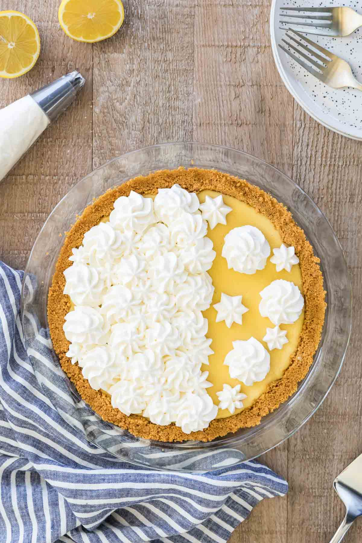 Lemon pie in a glass pie plate decorated with whipped cream.