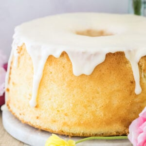 Golden chiffon cake with white glaze surrounded by a pink and yellow flower