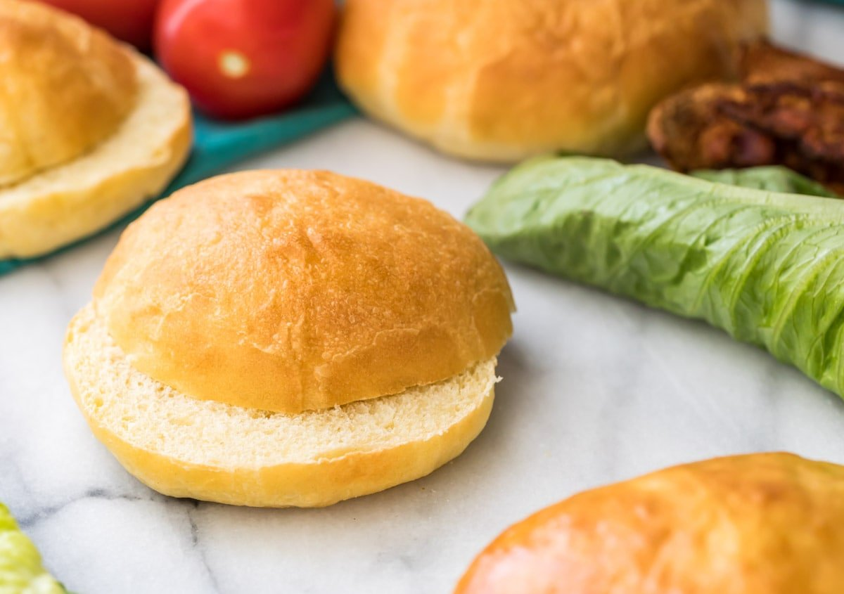sliced potato bun on marble with lettuce and more buns in background