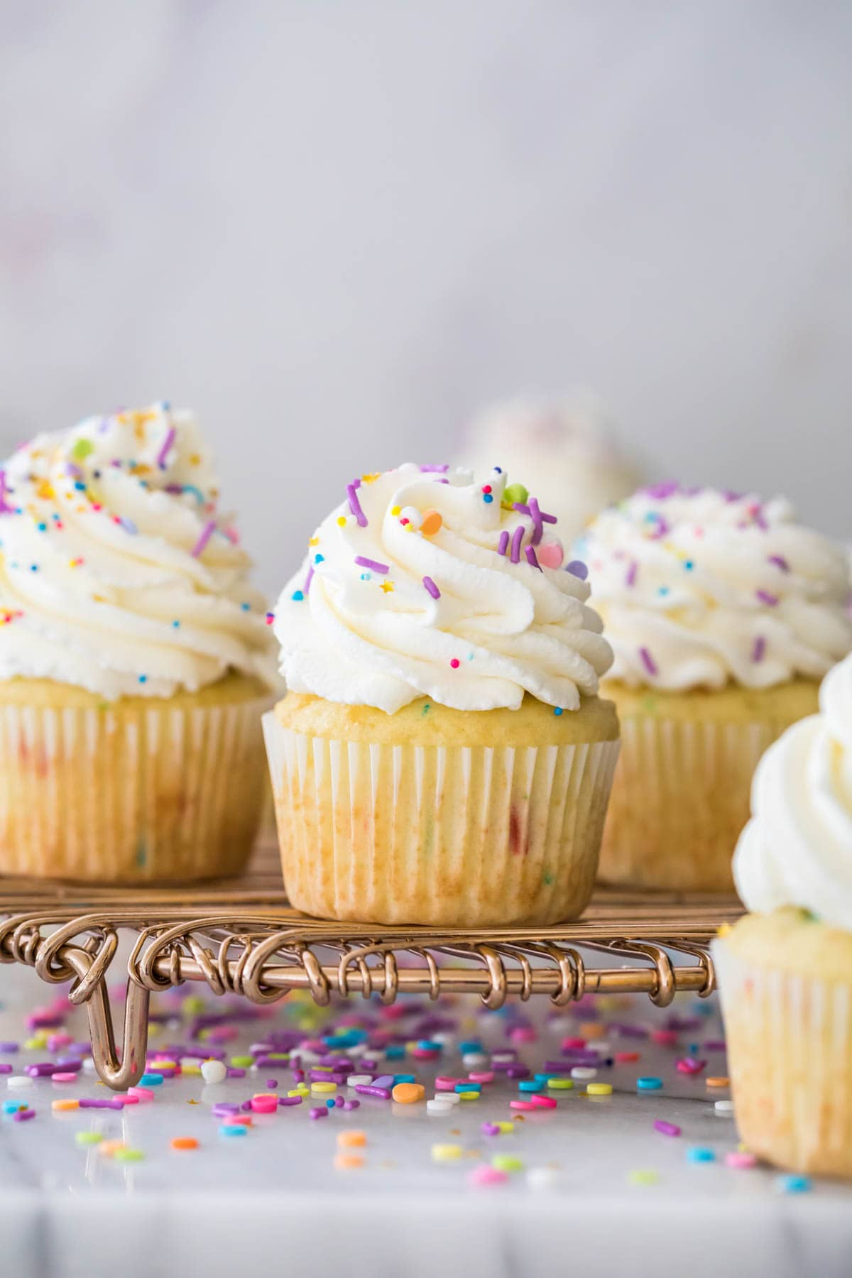 Closeup of vanilla sprinkle cupcake with whipped cream frosting and sprinkles, surrounded by more frosted cupcakes