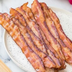 Strips of bacon in the oven on a round speckled white plate