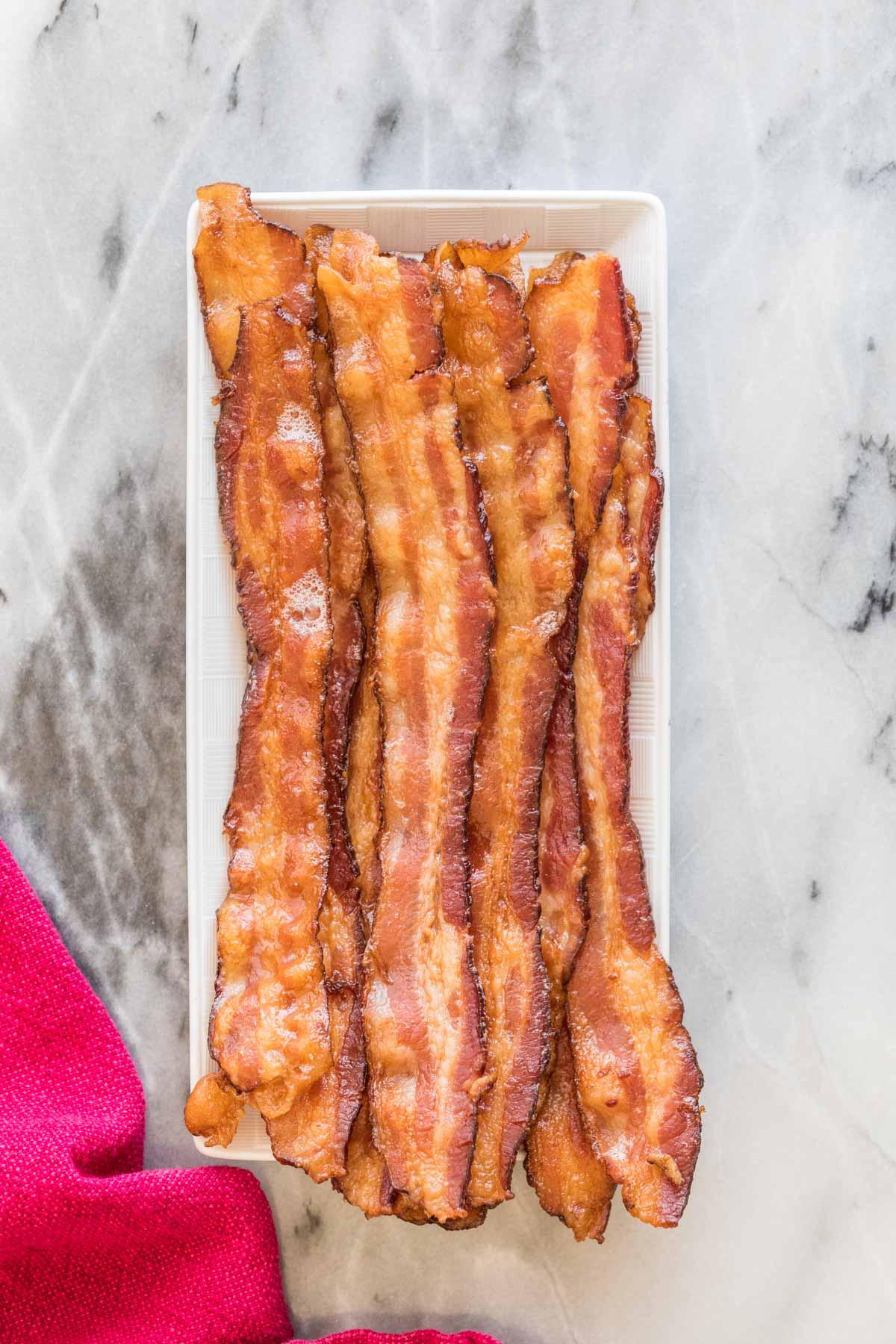 Overhead view of strips of crisp bacon arranged on a rectangular white platter