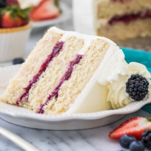 Three layer chantilly cake with berry filling on white plate surrounded by fruit