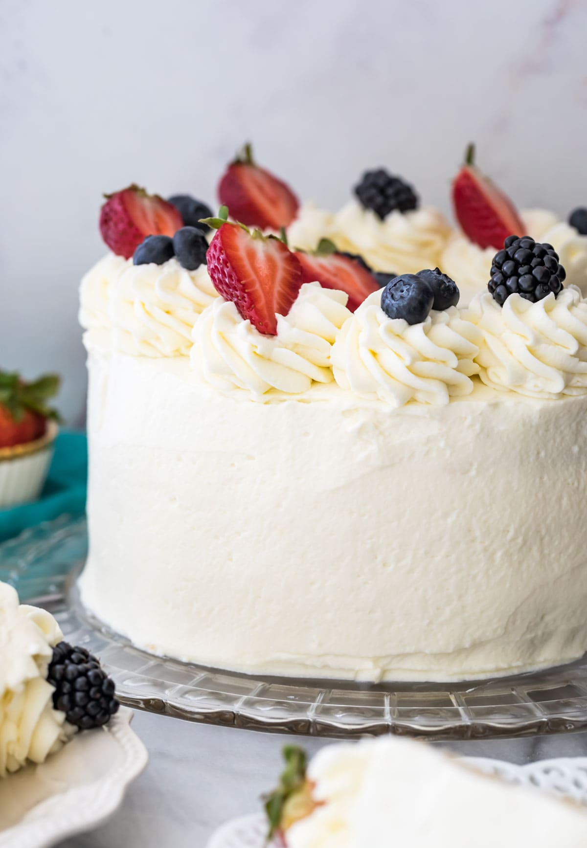 Chantilly cake on a glass platter, topped with fresh fruit