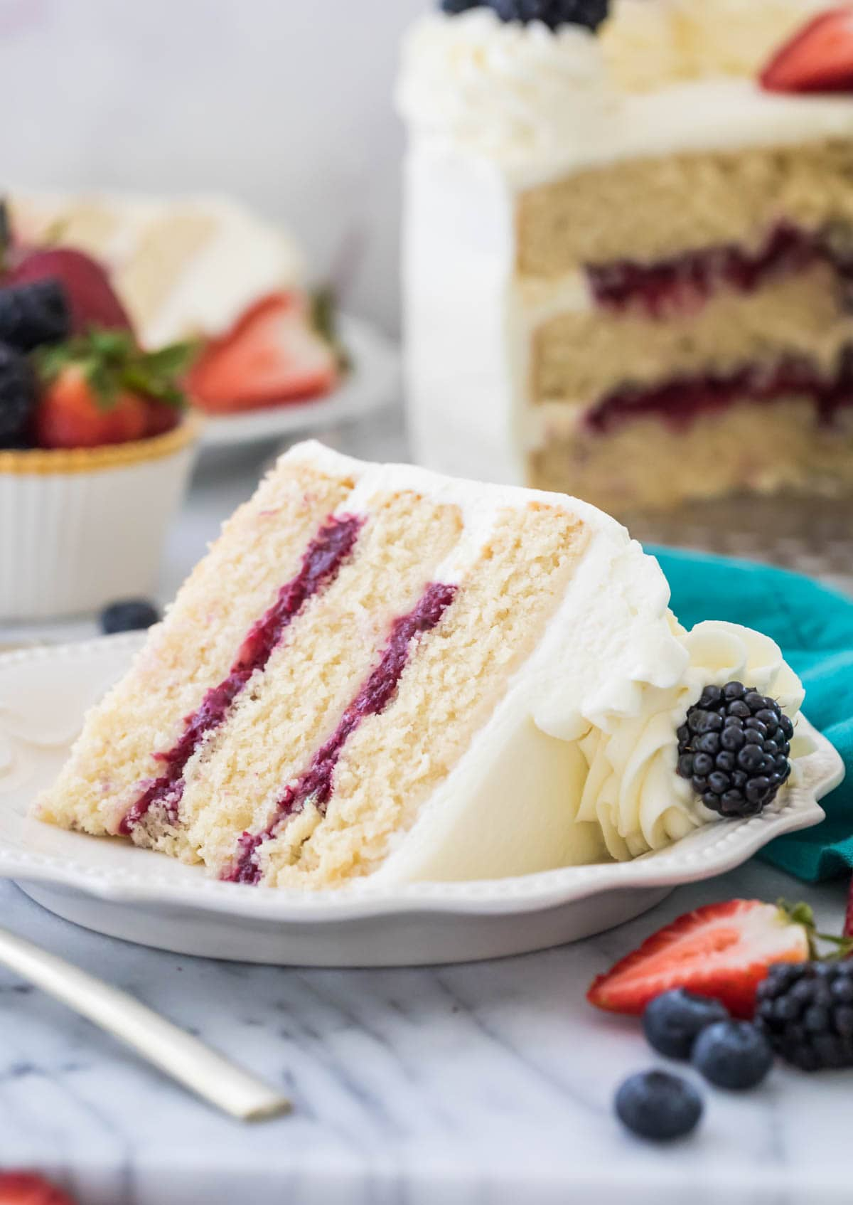 Three layer chantilly cake with berry filling on white plate surrounded by fruit and more cake