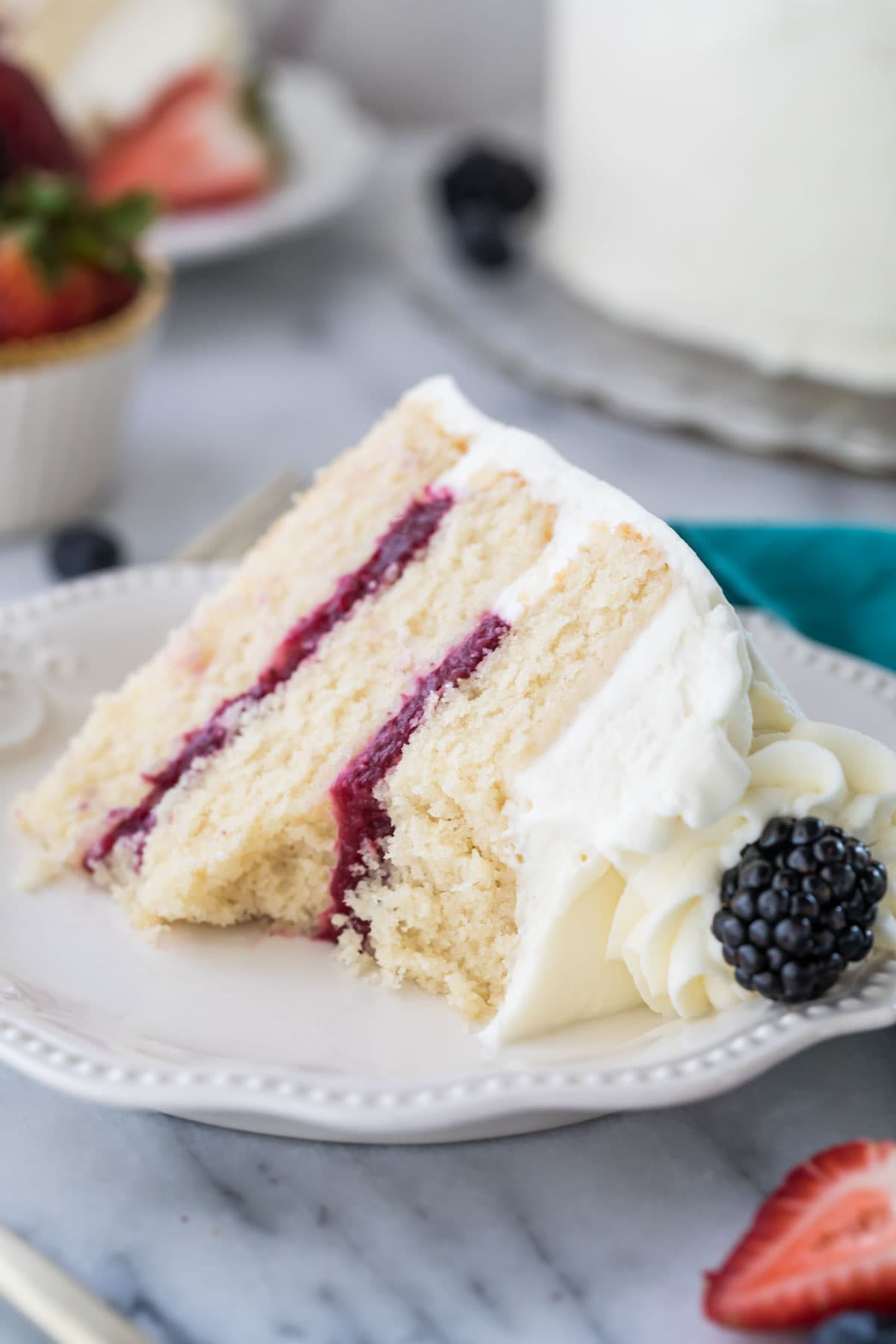 Slice of chantilly cake with a bite missing from it