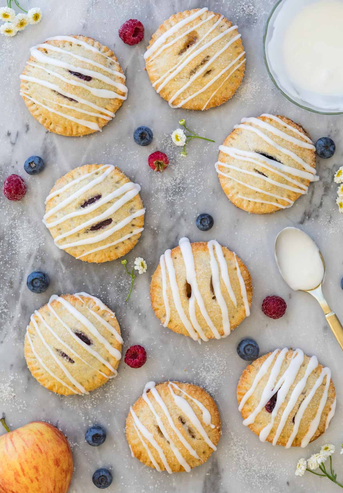 Overhead photograph of fruit-filled hand pies drizzled with vanilla glaze