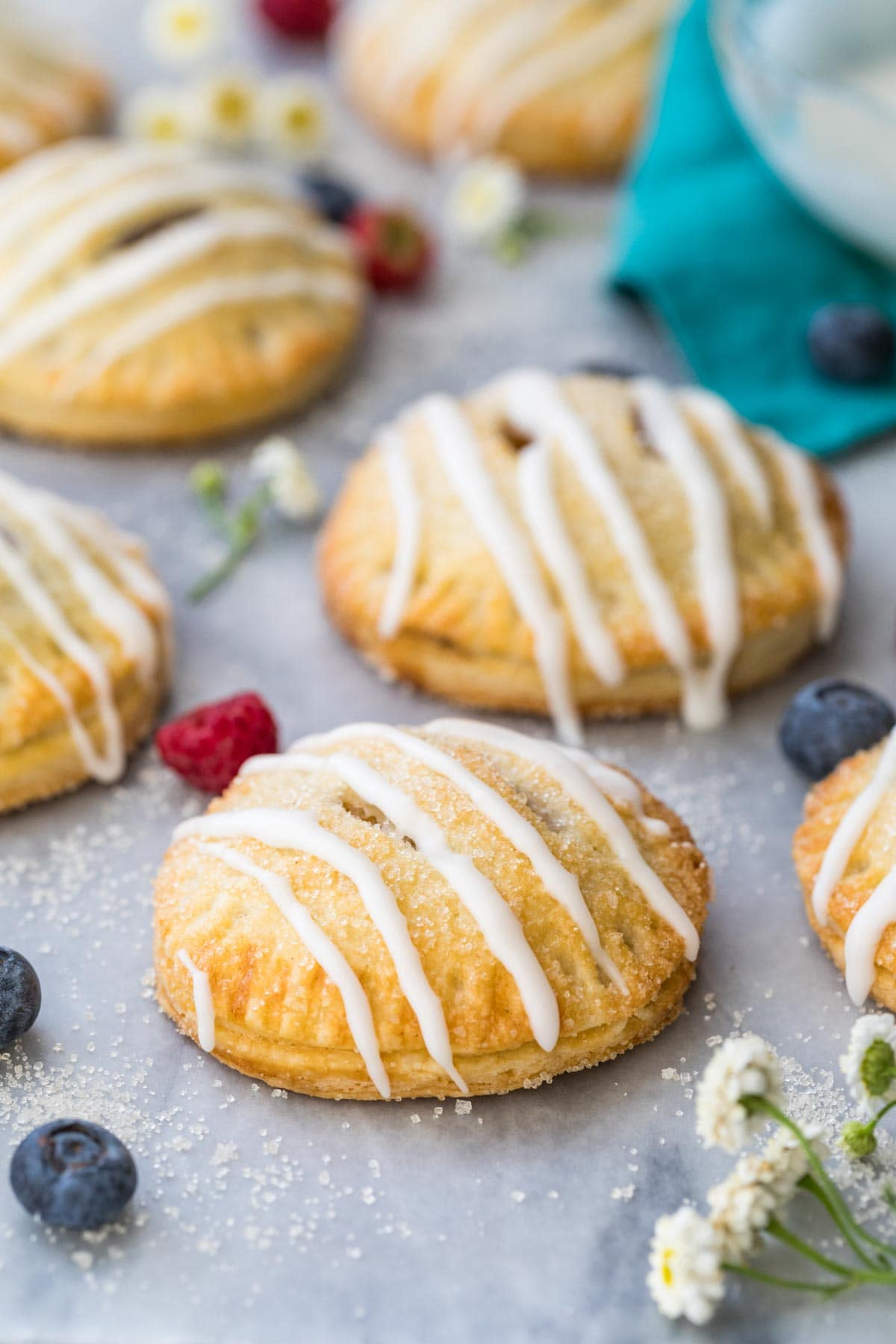 fruit-filled hand pies with vanilla glaze drizzle on marble