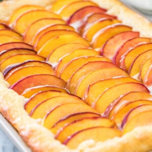 Close-up view of peach cake topped with sliced peaches in jellyroll pan