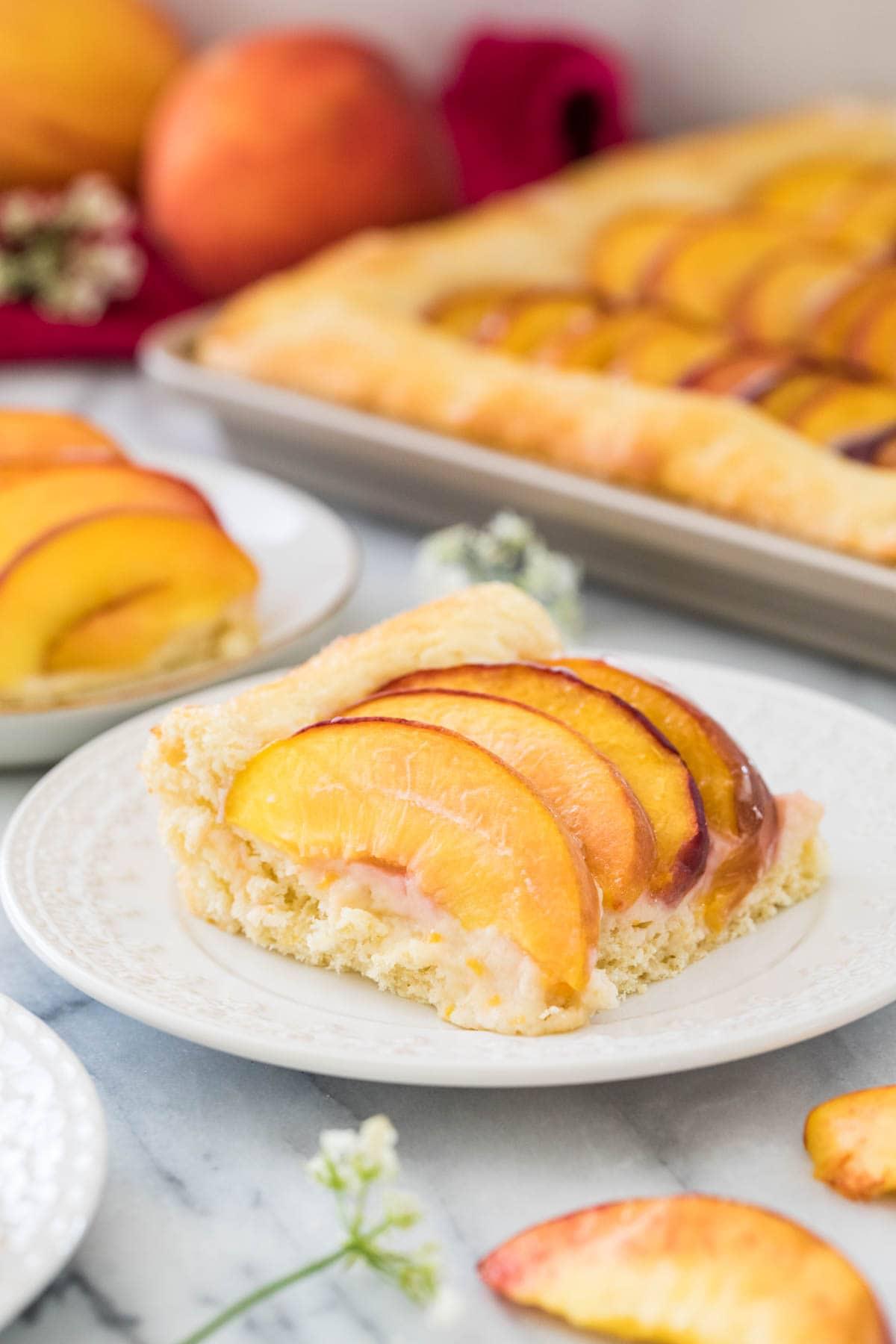 Slice of fresh peach cake on white plate