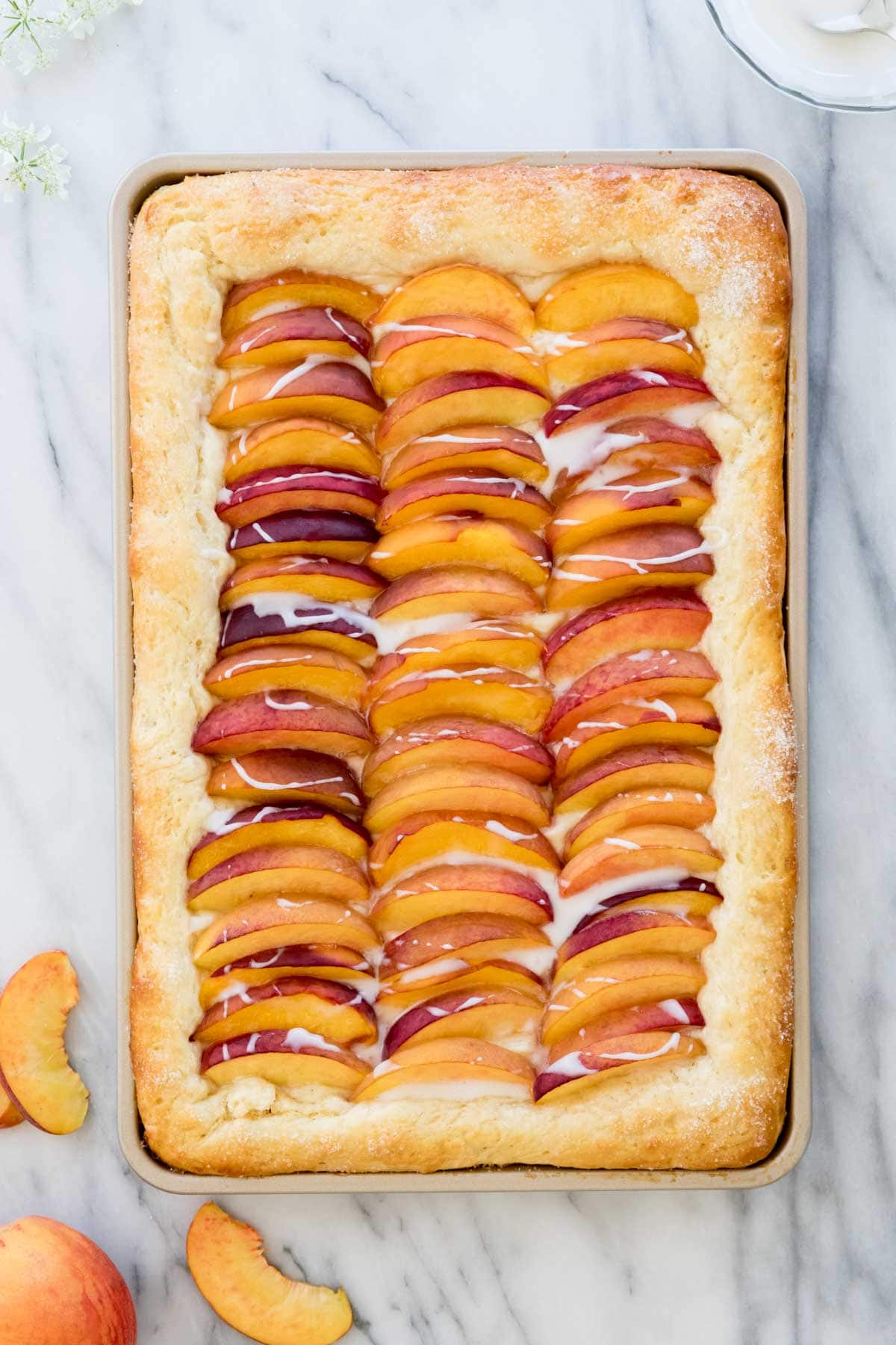 Overhead shot of peach cake in jellyroll pan topped with fresh sliced peaches