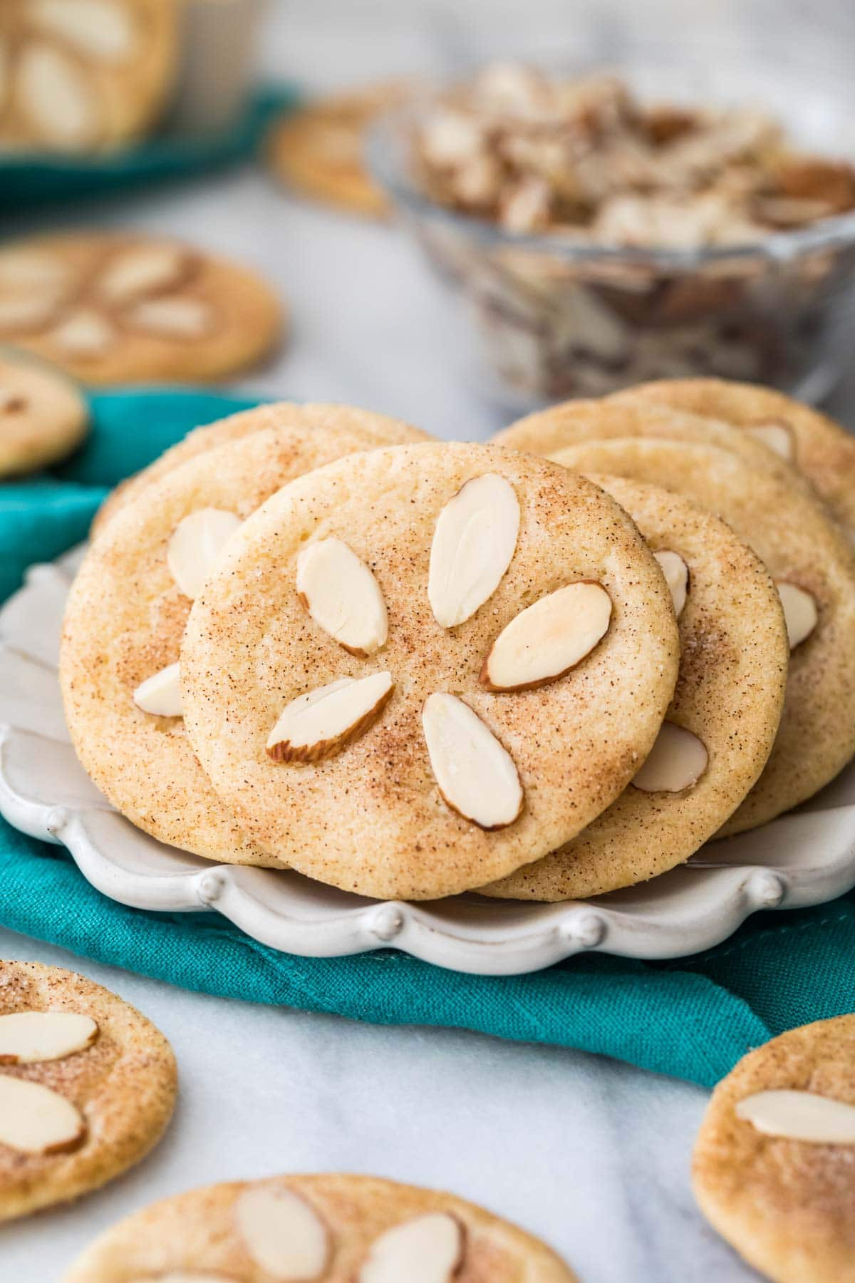Cookies decorated with almond slivers to look like sand dollars on white plate