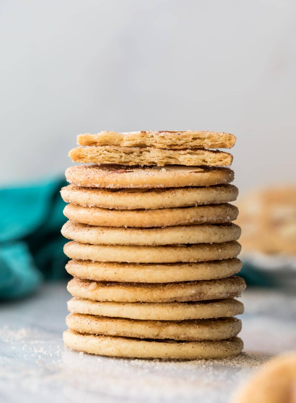 Stack of sand dollar cookies with cookie broken in half on top, showing that they are thin, crispy, and flat cookies