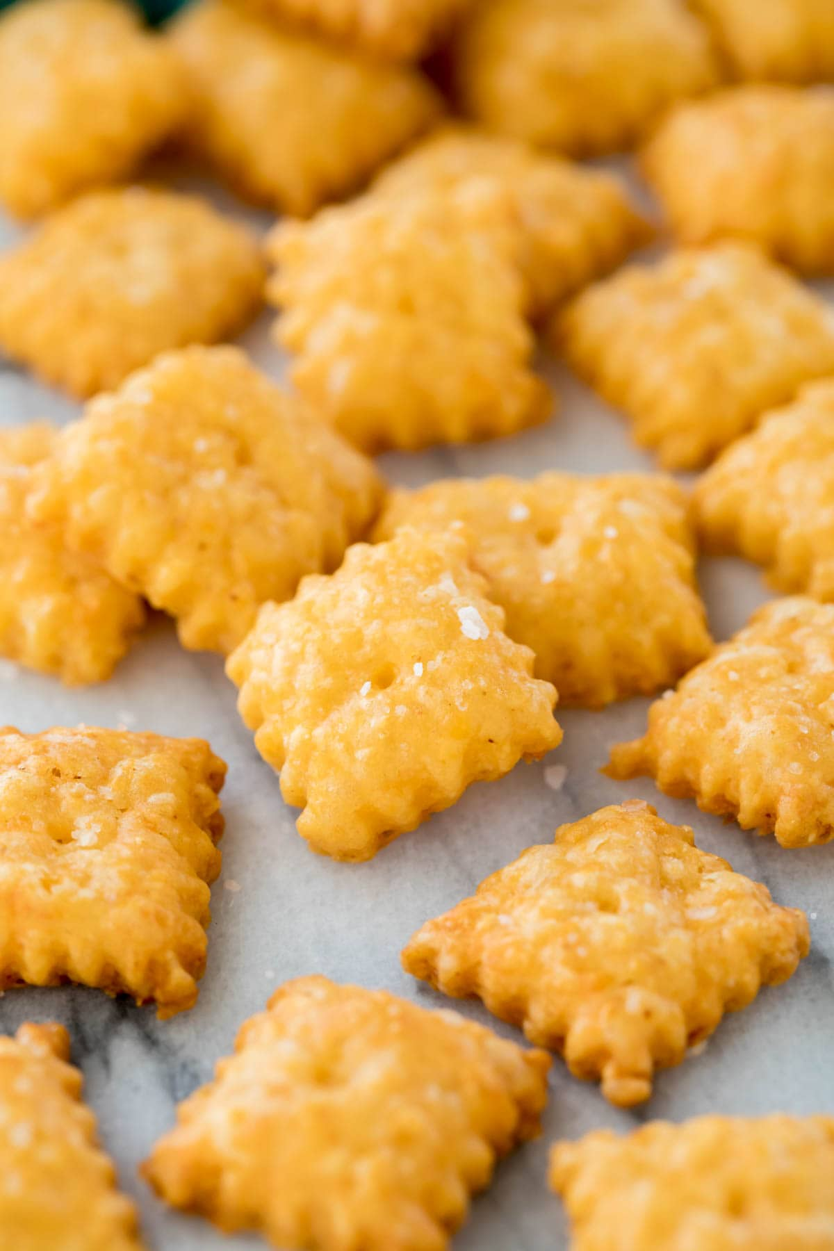 Zoomed-in view of homemade cheese crackers with frilled edges and topped with sea salt