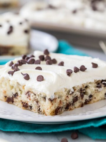 slice of chocolate chip sheet cake on a white plate on a teal towel