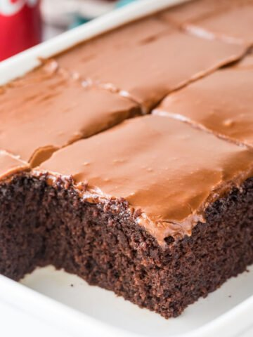 Thick squares of coca cola cake with shiny brown frosting in white cake pan