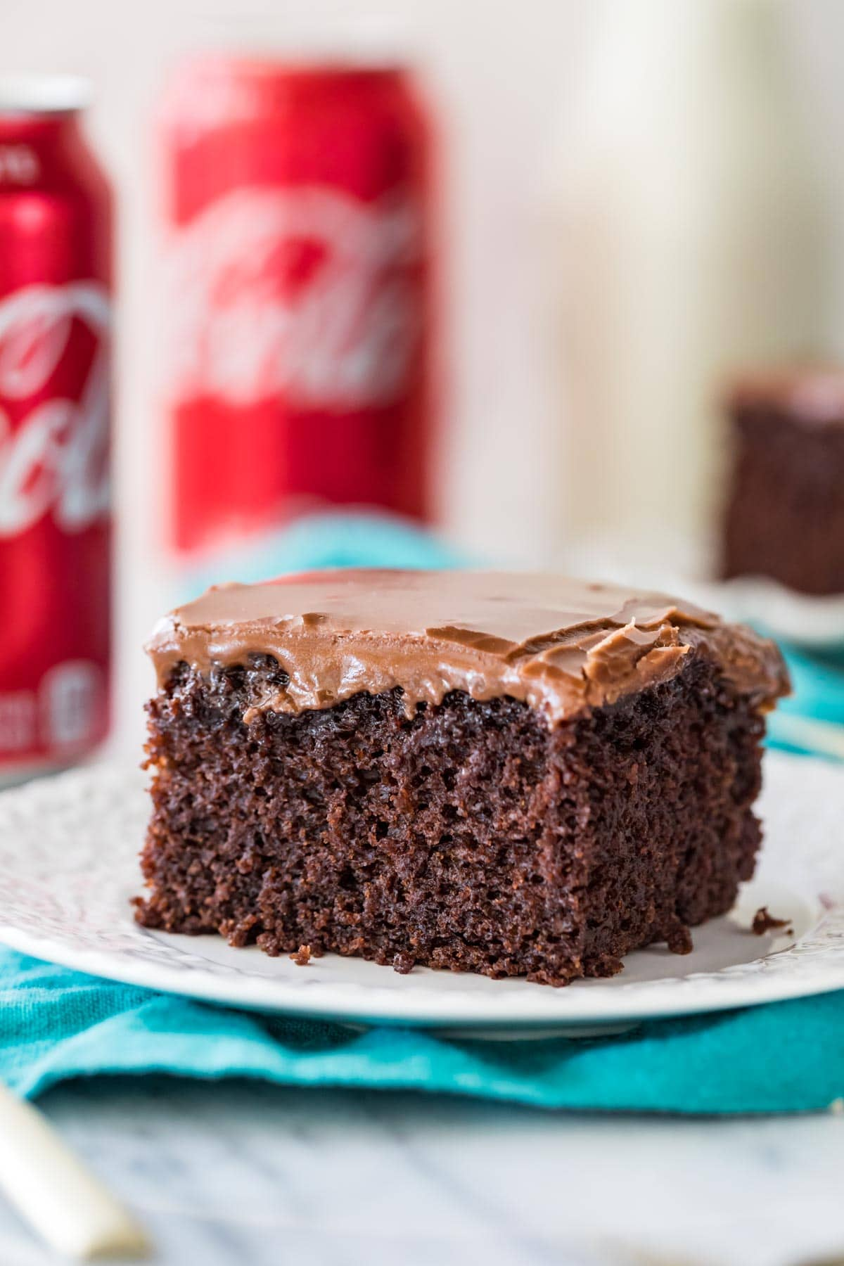 Close-up view of square piece of coca cola cake on white plate