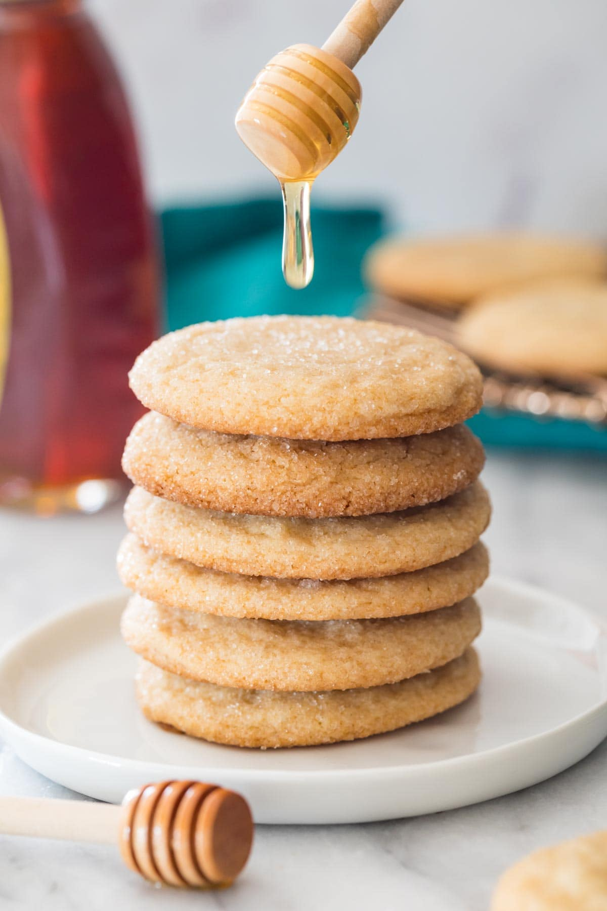 drizzling honey over a stack of honey cookies on white plate