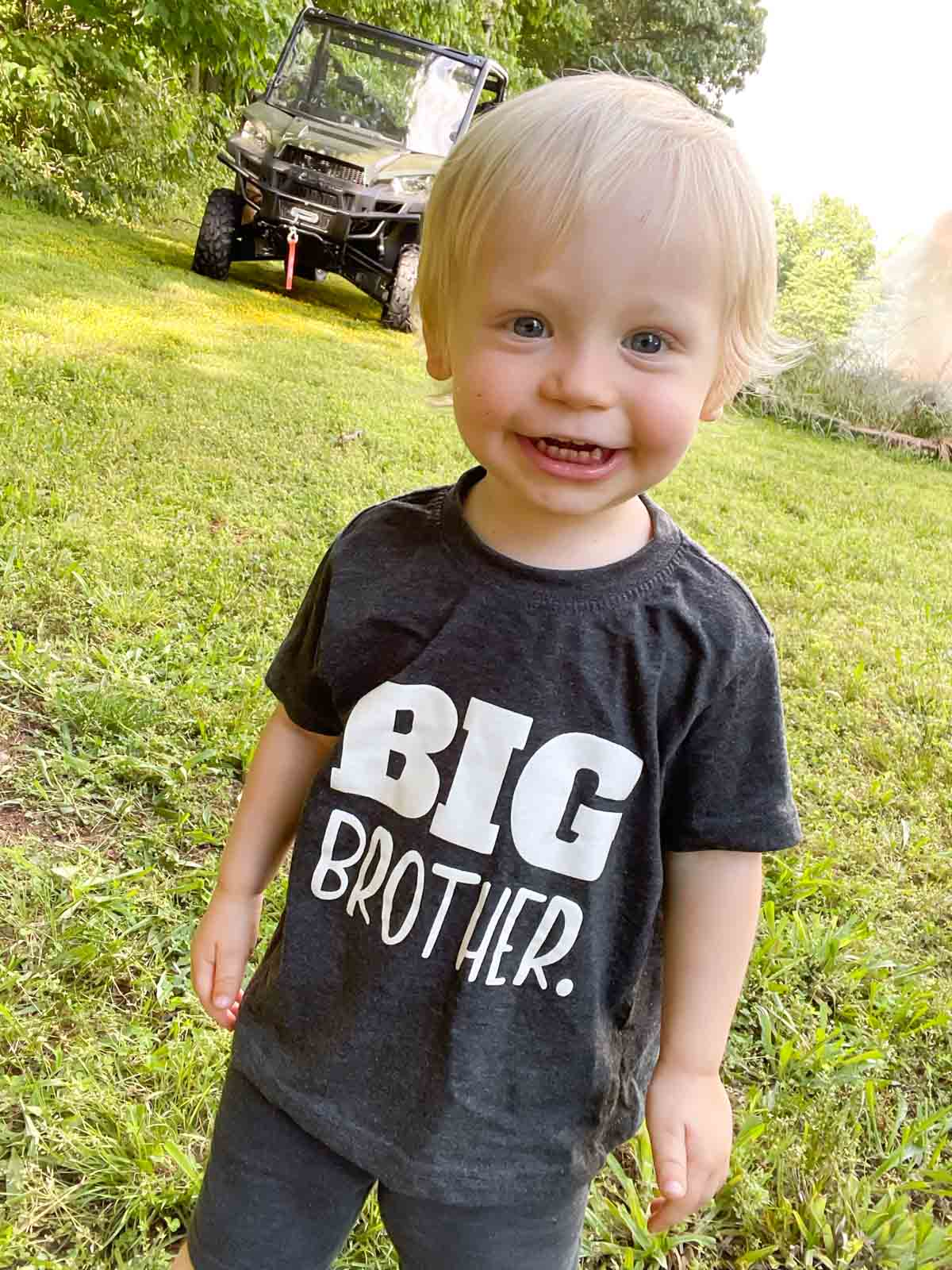 """Toddler boy in a grey shirt that reads """"BIG BROTHER"""". Photo taken outside, side by side in background"""