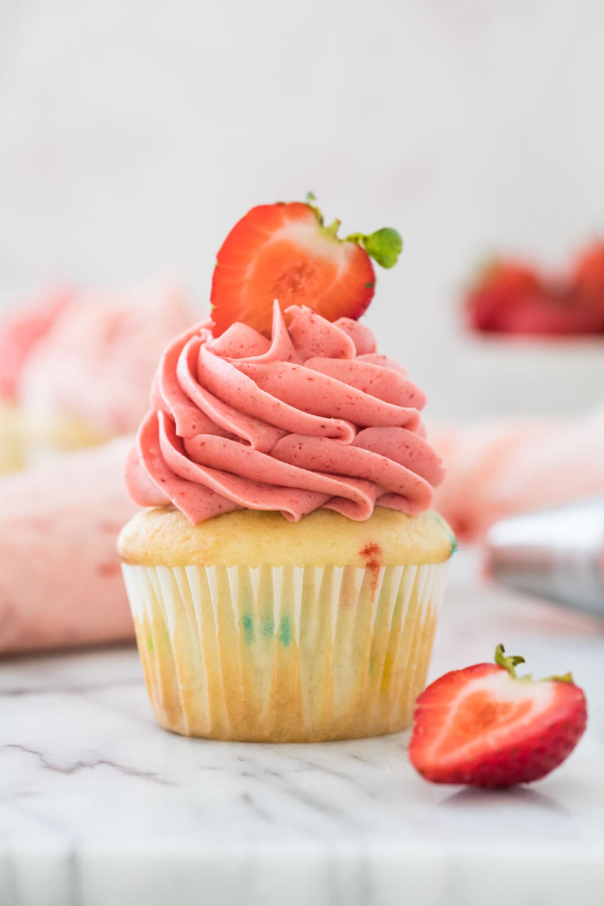 Vanilla cupcake topped with bright pink strawberry frosting and a halved fresh strawberry
