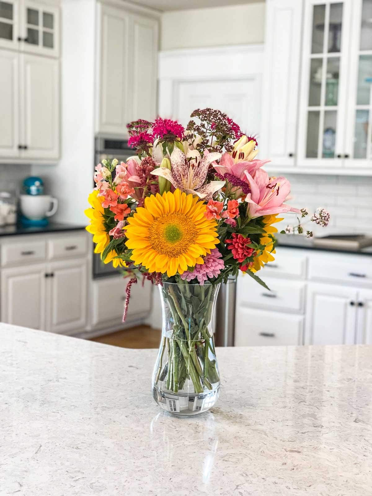 Glass vase with an array of multicolored flowers on white countertop