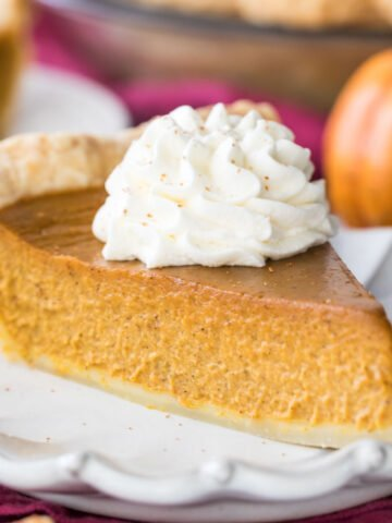 slice of homemade pumpkin pie topped with whipped cream on white plate