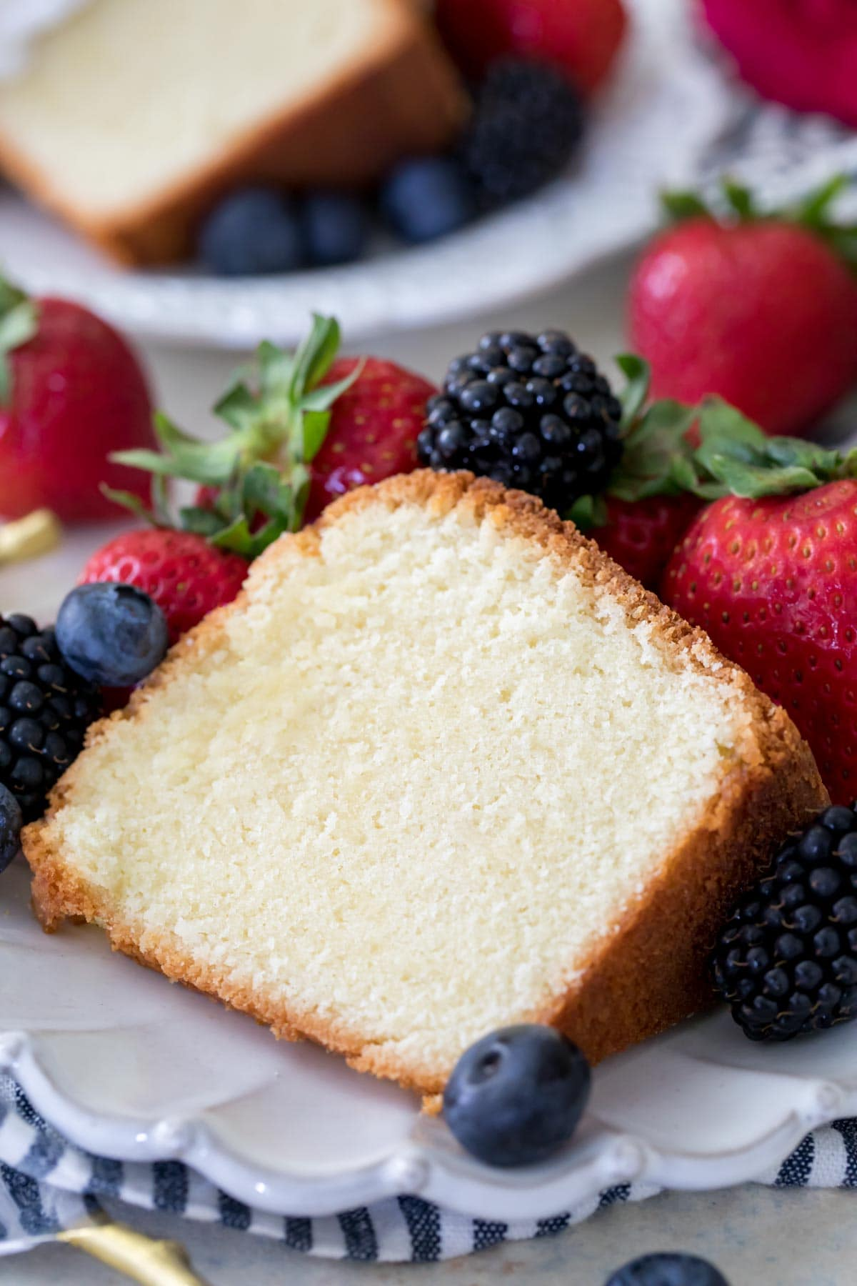 Thick slice of pound cake surrounded by fresh berries on white plate