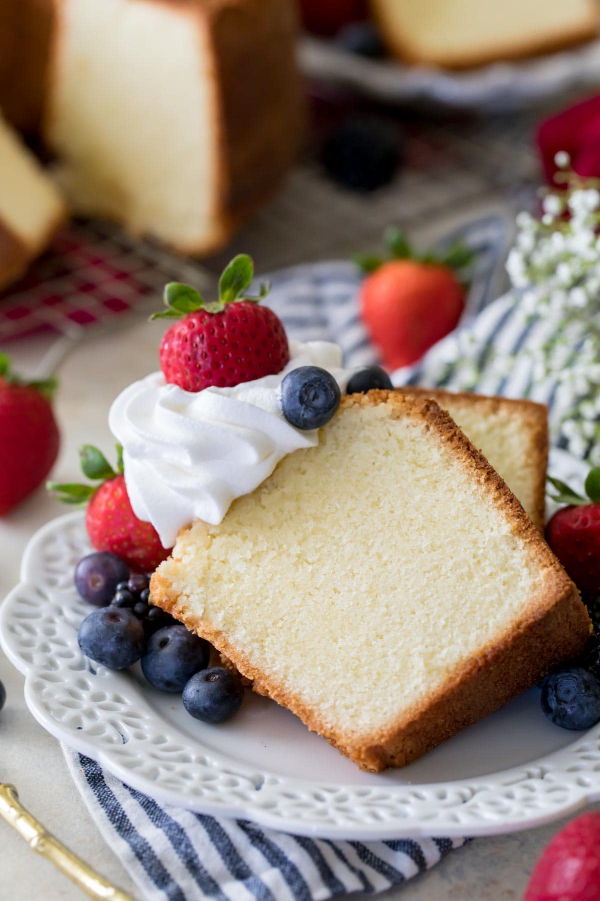 Two slices of pound cake topped with whipped cream and berries