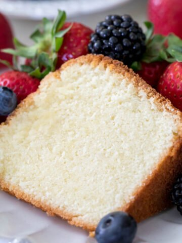 A slice of moist, buttery pound cake surrounded by fresh berries on a white plate