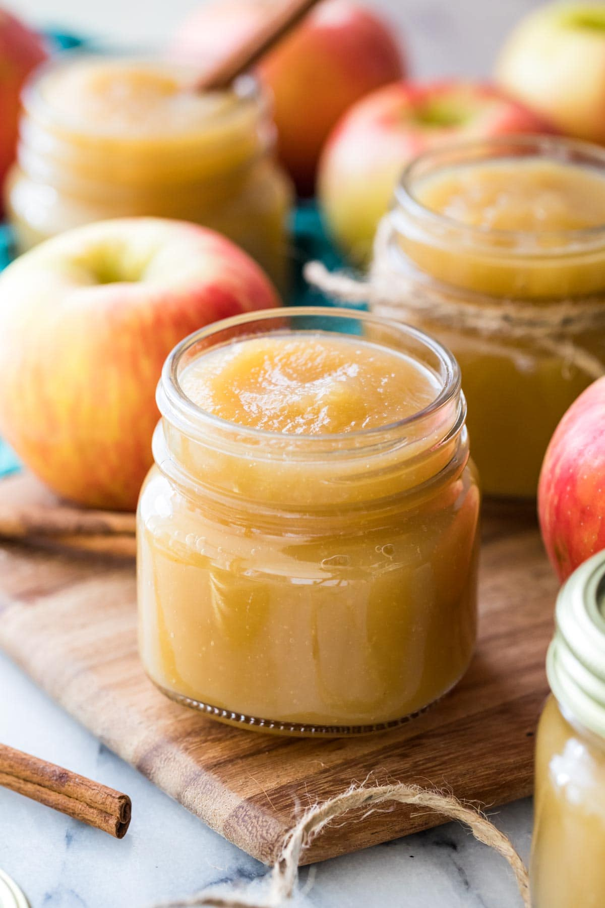 Clear glass jars filled with golden colored applesauce with red apples intermingled