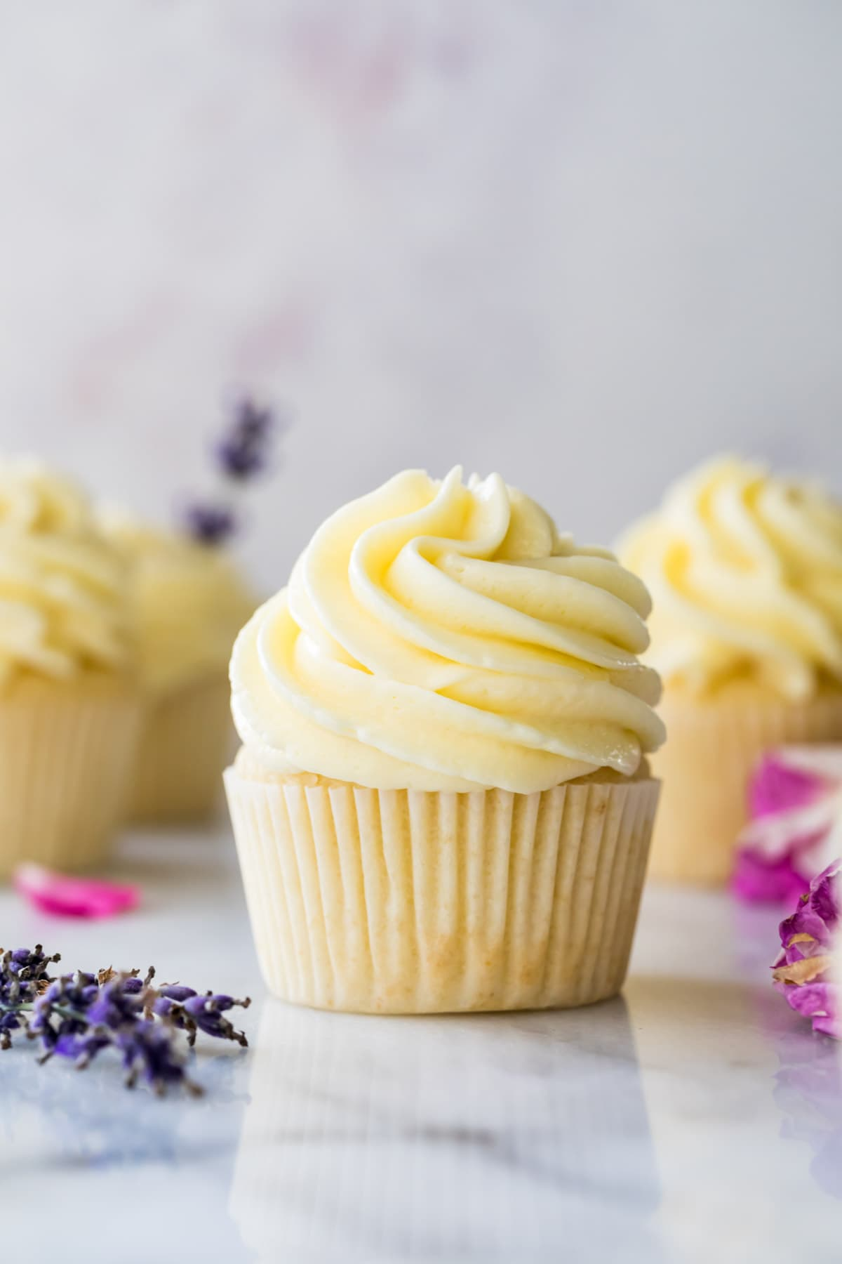 Cupcake topped with German buttercream frosting surrounded by other cupcakes