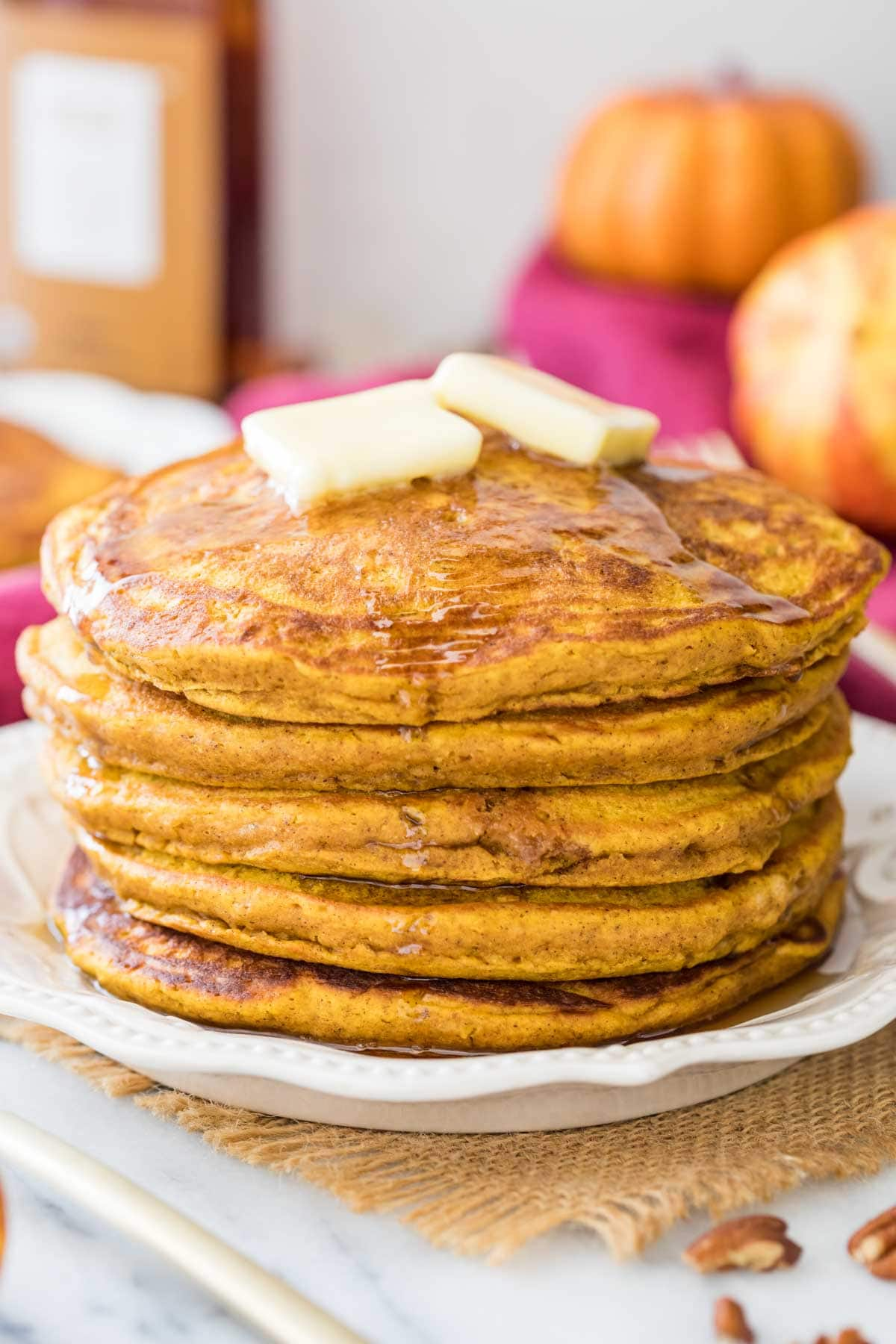 stack of pumpkin pancakes drizzled with maple syrup and topped with butter