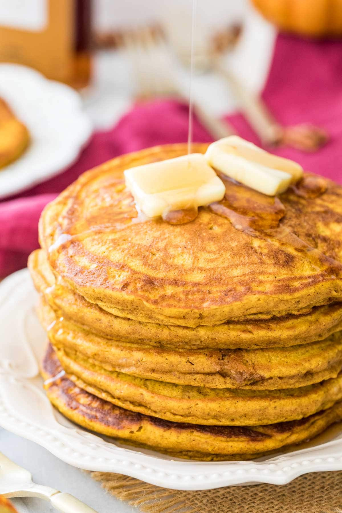 thick, fluffy pumpkin pancakes being drizzled with maple syrup