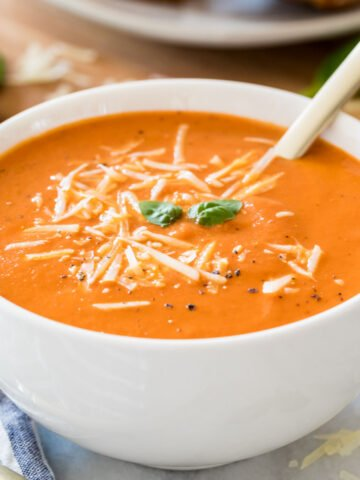 white bowl of hearty homemade tomato soup garnished with parmesan cheese, fresh basil, and cracked black pepper