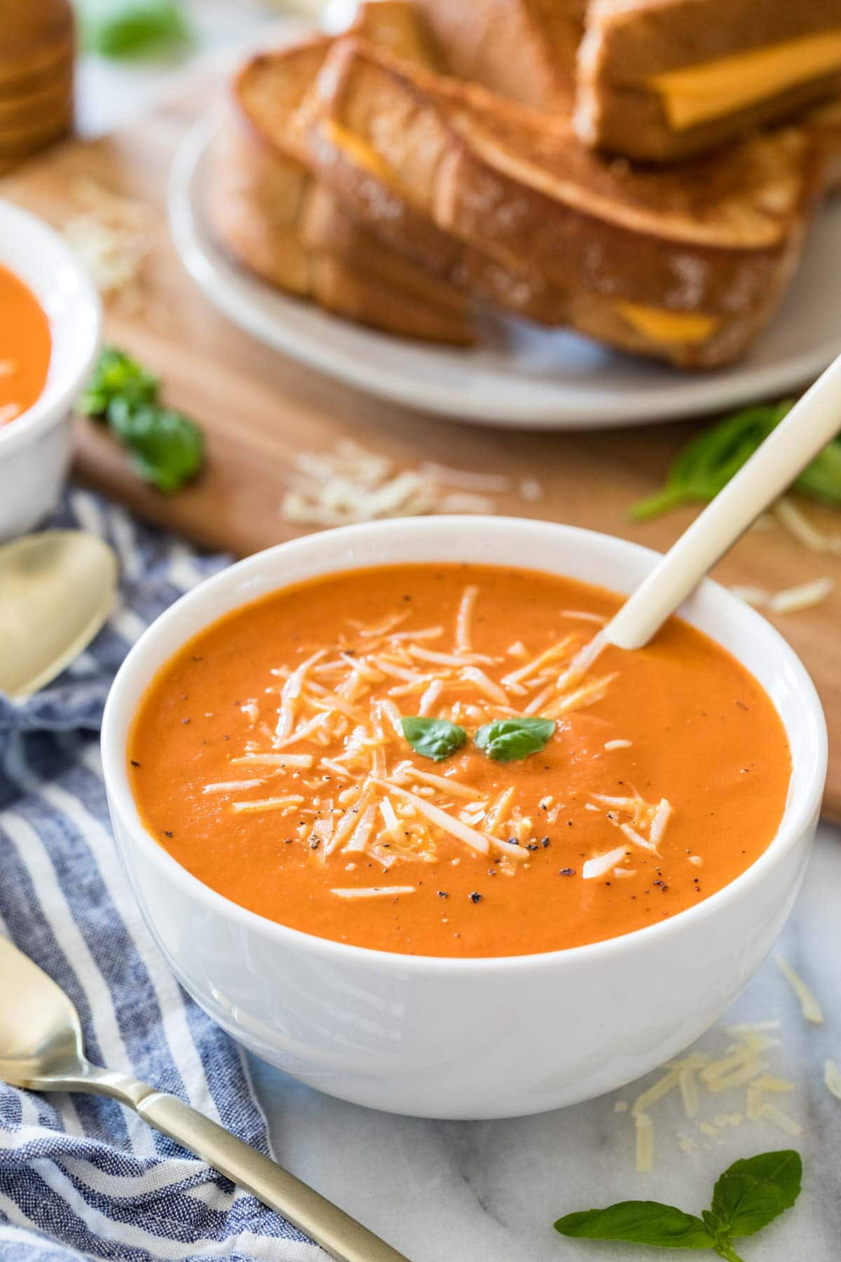 velvety tomato soup topped with cheese and fresh basil in white bowl with spoon dipped into it